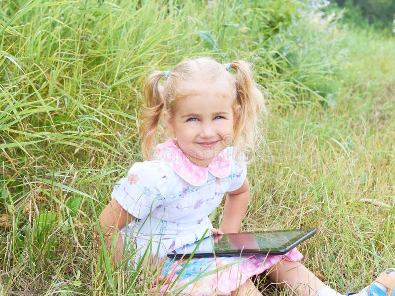 Liten flickasammanträde parkerar på solig dag och spelar in med minnestavlaPC arkivbild