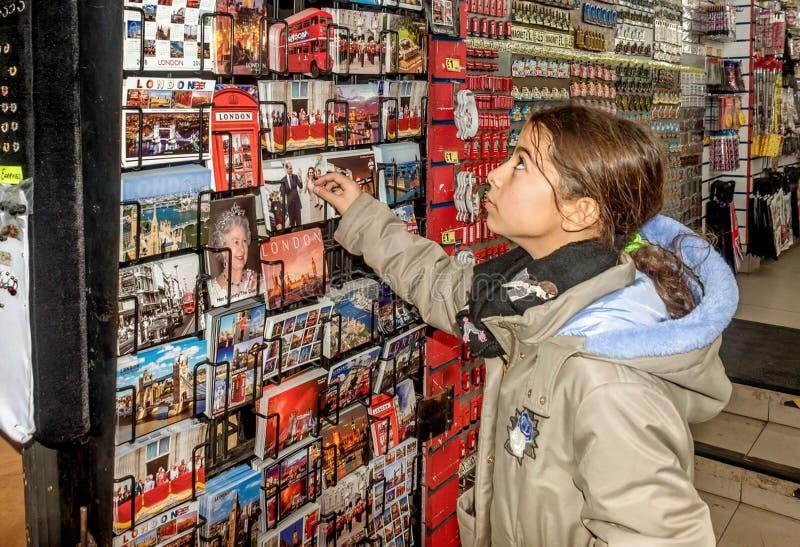 Liten flickashopping för vykort i London, UK arkivfoton
