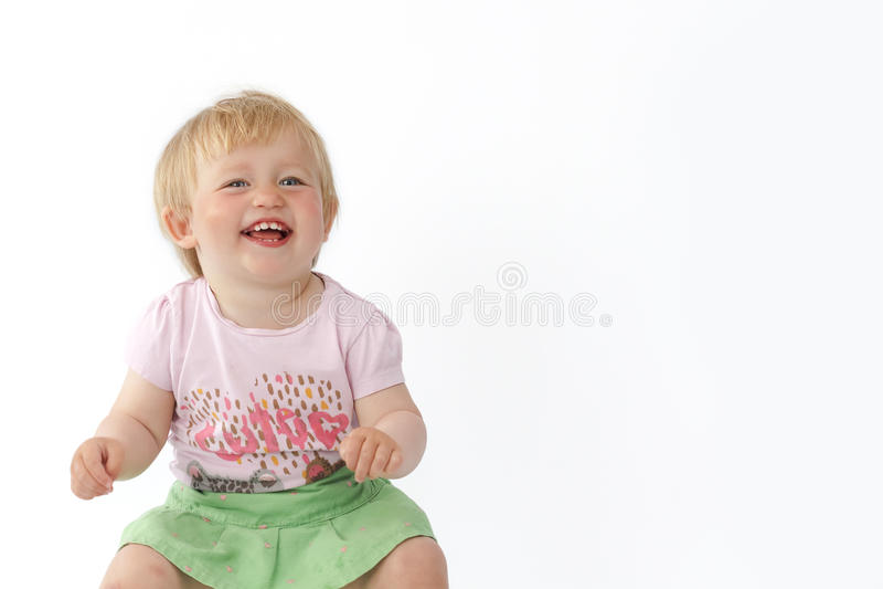 Liten flickaskratt och blickar på kameran fotografering för bildbyråer