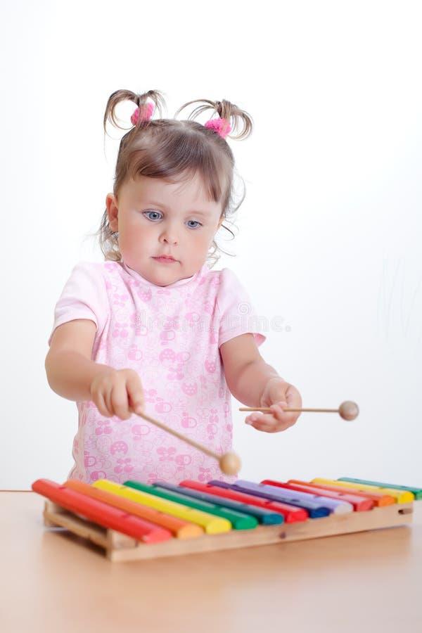 Liten flickaspelrum på xylofon arkivfoton