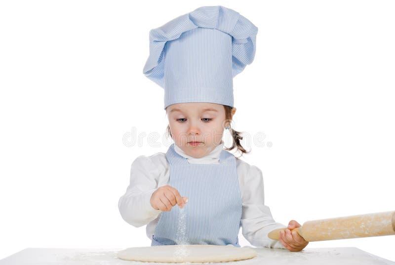 Liten flickastänkmjöl på pizzadeg arkivfoto