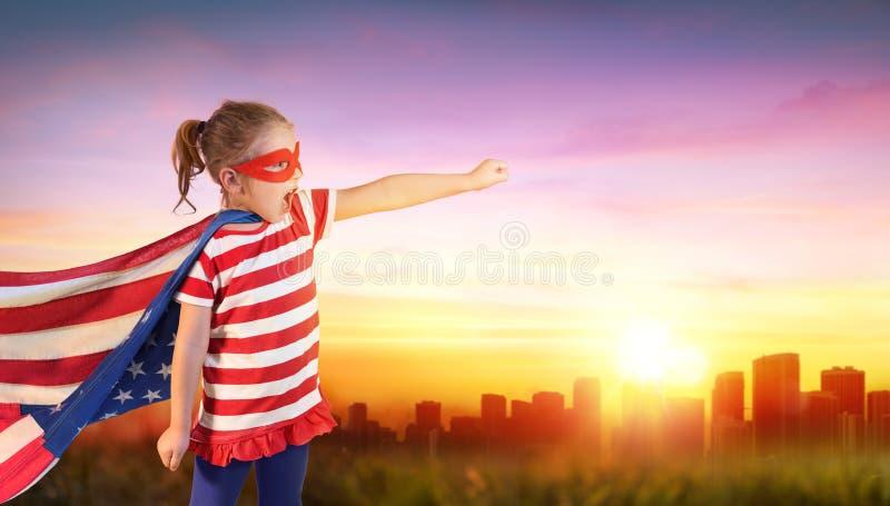 Liten flickaSuperhero av USA med Cityscape royaltyfria foton