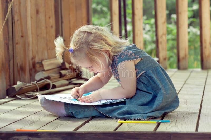 Liten flickateckning med kulöra blyertspennor på ett trä för landshus fotografering för bildbyråer