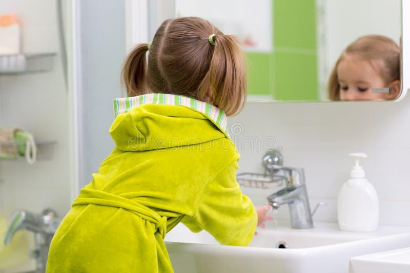Liten flickatvagninghänder i badrum royaltyfri foto