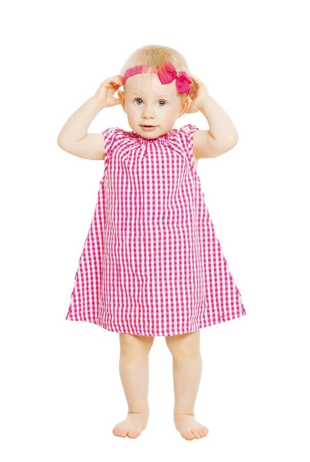 Liten flickaunge i röd klänning med pilbågen Barn som isoleras på vit b arkivfoton