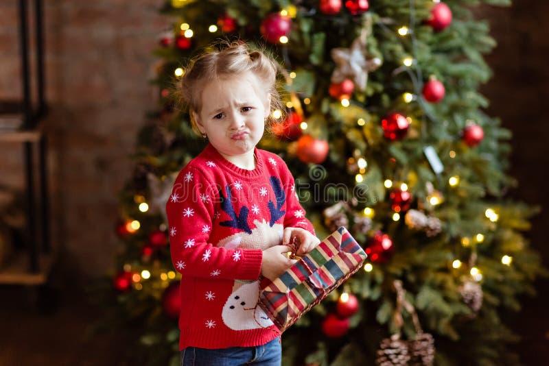 Liten flickaungen i den röda tröjan som rymmer en gåva och, gör framsidan royaltyfria foton