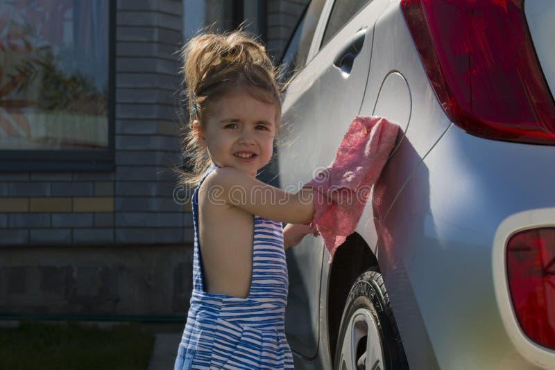 Liten flickawash en bil Bil för rengöring för barnportionfamilj fotografering för bildbyråer