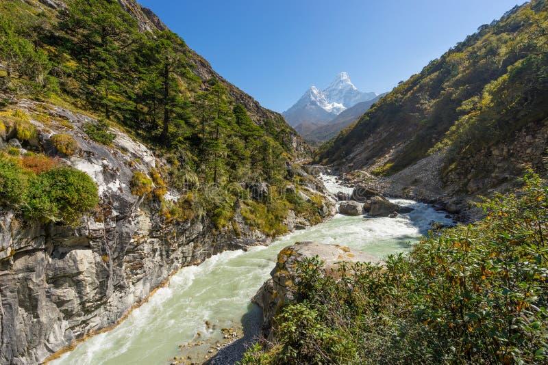 Liten flod med Ama Dablam bergbakgrund, Everest region, fotografering för bildbyråer
