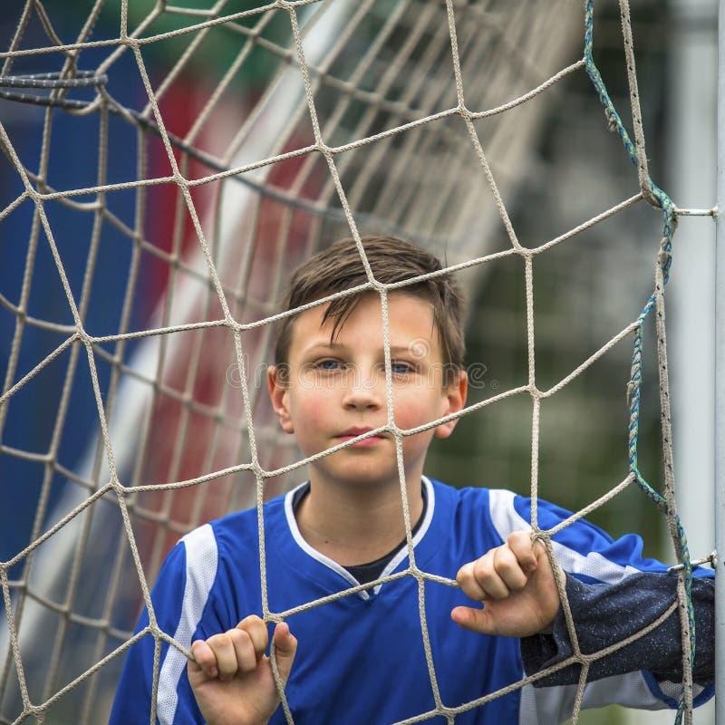 Liten fotbollsspelare bak fotbollmålet sport royaltyfri bild