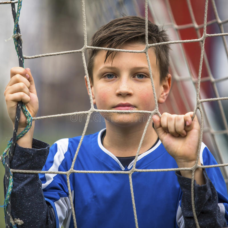 Liten fotbollsspelare nära portarna av stadion sport arkivbild
