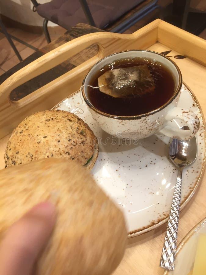 Liten frukost med brödrullar för svart te och för helt vete fotografering för bildbyråer