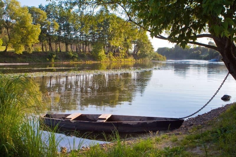 Liten gammal använd träfiska stakbåt på banken av en flod, solig dag för ljus sommar arkivfoton