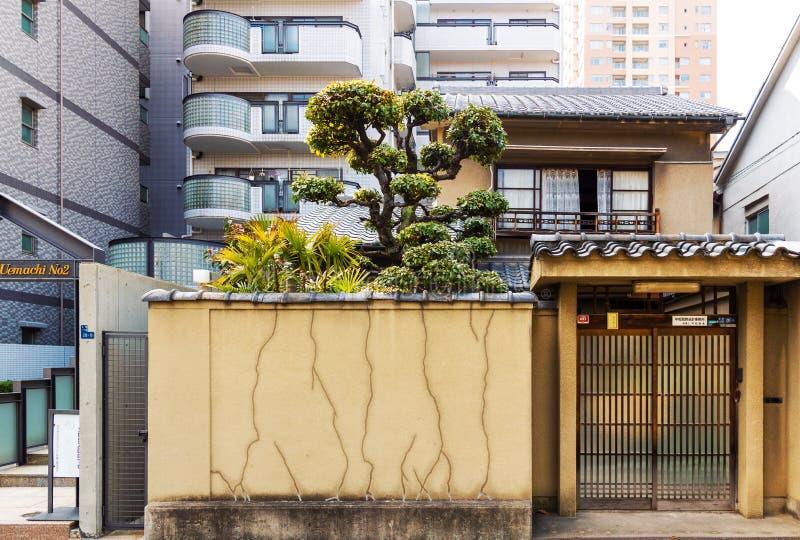 Liten gammal japansk husfasad i bakgrunden av höga bostads- byggnader i Japan arkivfoton