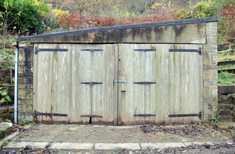 Liten gammal stenlagring eller garagebyggnad med att förfalla trädörrar och rostade gångjärn med det fuktiga väggar och taket royaltyfri bild