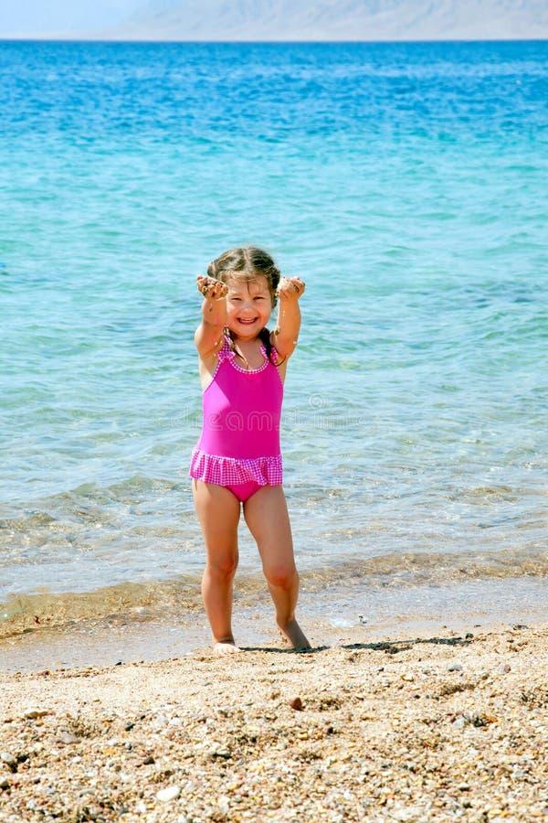 Liten gir som spelar med sanden på stranden. royaltyfri fotografi