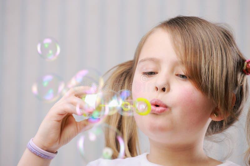 Liten girll som blåser bubblor royaltyfri bild