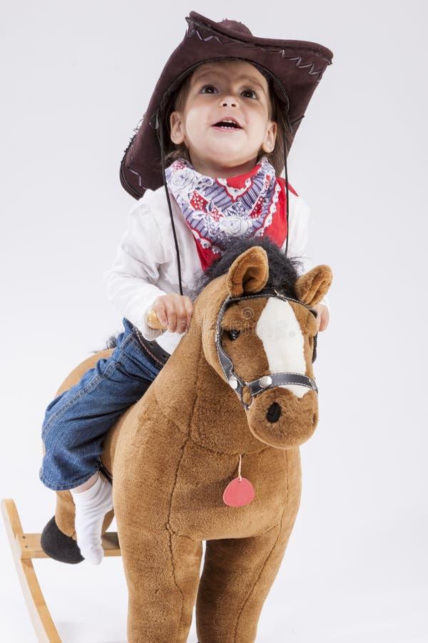 Liten gladlynt Caucasian flicka i cowgirlkläder som rider Toy Horse royaltyfri bild
