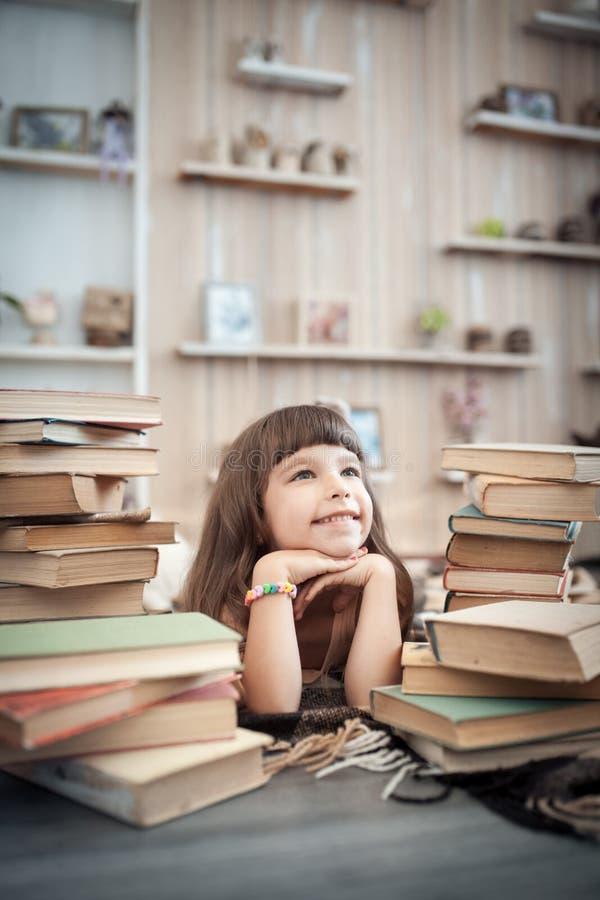 Liten gladlynt flicka med bunten av böcker i arkiv; royaltyfria bilder