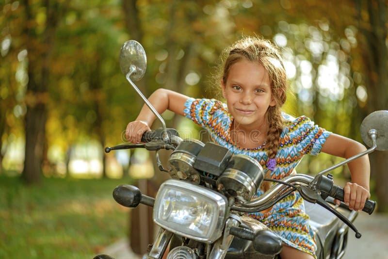 Liten gladlynt flicka på den gamla cykeln arkivbild