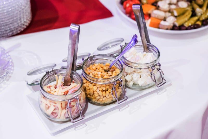 Liten glass krus för Antipastiaptitretare som är välfylld med ostfetalöken och havre för sallad på den vita plattan arkivfoton