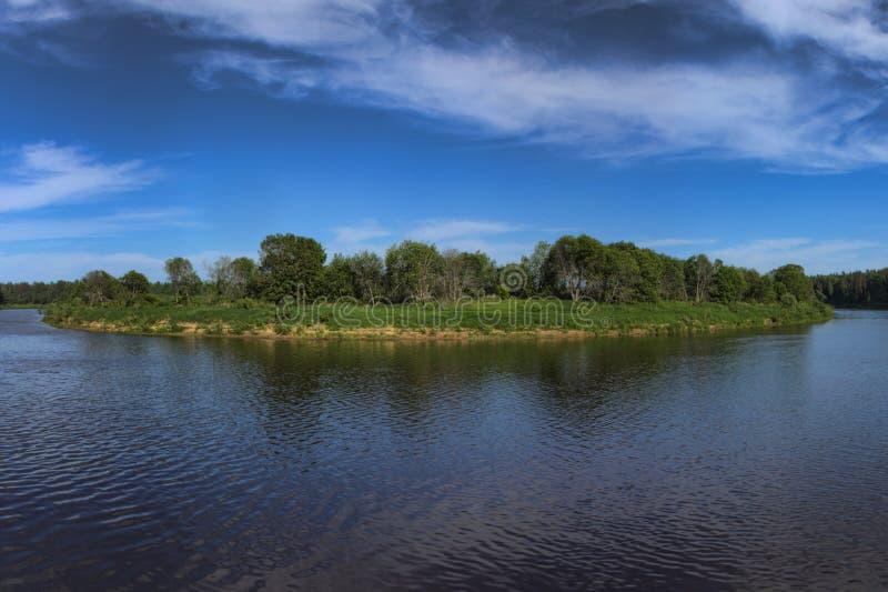 Liten grön ö i den blåa sjön royaltyfri fotografi