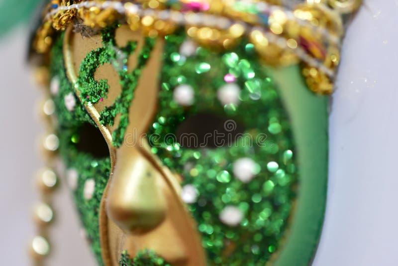 liten grön och guld- karnevalmaskering fotografering för bildbyråer