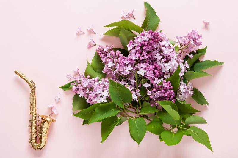 Liten guld- saxofon och bukett av den nya doftande rosa lilan på rosa pappers- bakgrund B?sta sikt, n?rbild arkivbilder