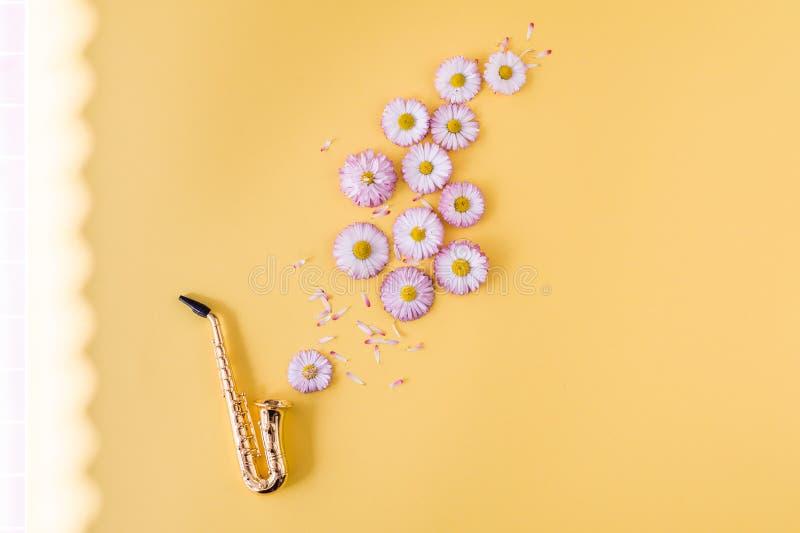 Liten guld- saxofon och rosa tusensk?nor p? orange bakgrund arkivfoton