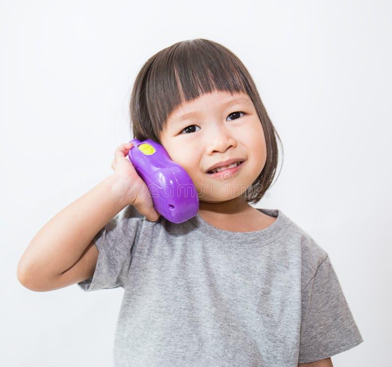 Liten gullig asiatisk flicka som talar med den plast- telefonen royaltyfri bild