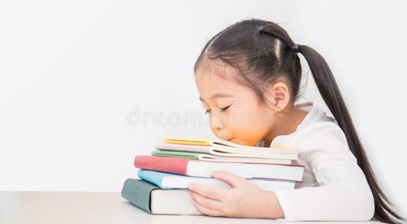 Liten gullig asiatisk flickasömn på bunt av böcker försökte från skola arkivbild