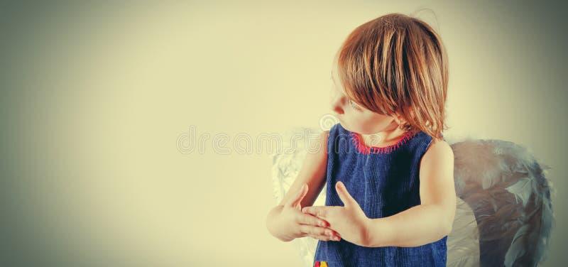 Liten gullig barnflicka för ängel med vingar som så gör handgester, om hon som rymmer a, behandla som ett barn utformat retro royaltyfri foto