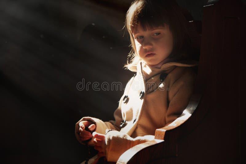 Liten gullig barnflicka som ber i kyrkan f?r begreppskor f?r bakgrund tr?plattform text f?r brunt avst?nd f?r tro fritt litet fotografering för bildbyråer