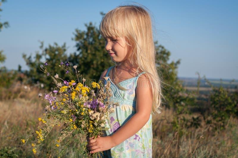 Liten gullig blond flicka i ett fält på en solig dag med en bukett av lösa blommor royaltyfria bilder
