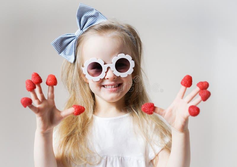 Liten gullig blond flicka med hallon i hennes fingrar, olika sinnesrörelser, inomhus royaltyfria foton