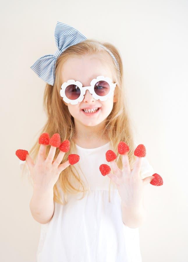 Liten gullig blond flicka med hallon i hennes fingrar, olika sinnesr?relser, inomhus royaltyfri bild
