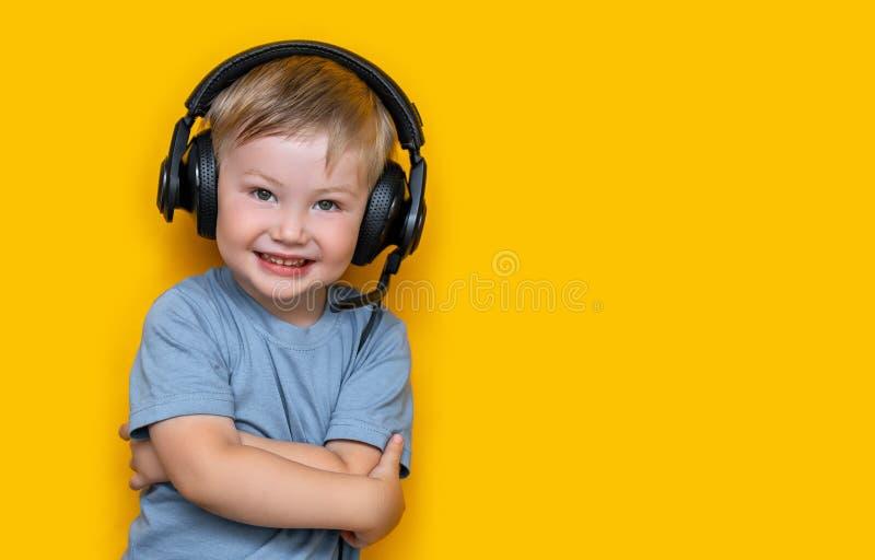 Liten gullig caucasian blond pojke i hörlurar som poserar lyckligt le som isoleras på gul bakgrund arkivfoto