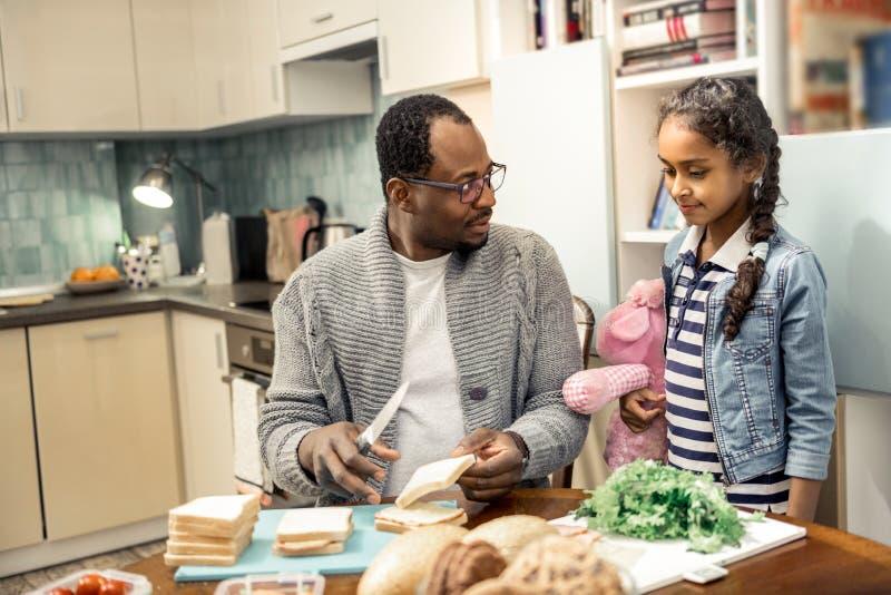 Liten gullig dotter som kommer till kök som ser fadern framställning smörgåsar arkivfoton