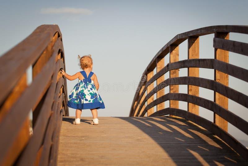 Liten gullig elegant flicka i härligt klänninganseende på träbron arkivbilder
