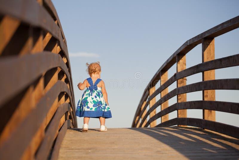 Liten gullig elegant flicka i härligt klänninganseende på träbron arkivfoto