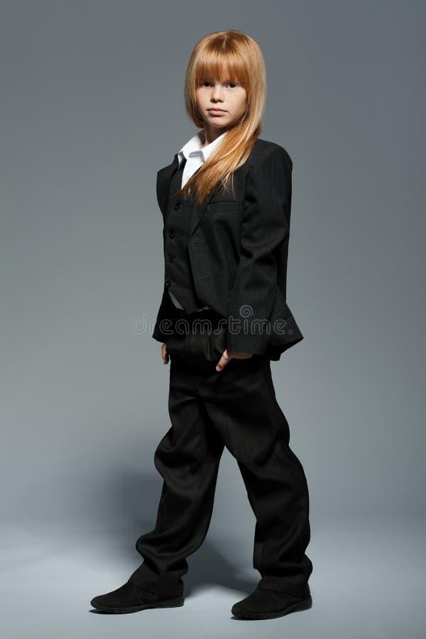 Liten gullig flicka i svart omslag, i svart byxa som isoleras över grå bakgrund arkivbild
