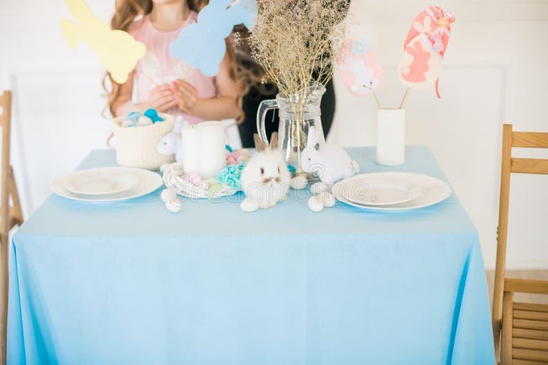 Liten gullig flicka med l?ngt lockigt h?r med sm? kaniner och p?skdekoren hemma p? tabellen arkivbild