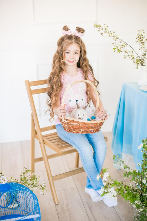 Liten gullig flicka med l?ngt lockigt h?r med sm? kaniner och p?skdekoren hemma p? tabellen arkivfoto