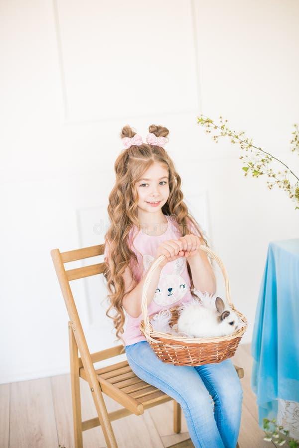 Liten gullig flicka med l?ngt lockigt h?r med sm? kaniner och p?skdekoren hemma p? tabellen fotografering för bildbyråer