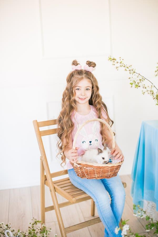 Liten gullig flicka med l?ngt lockigt h?r med sm? kaniner och p?skdekoren hemma p? tabellen arkivbilder