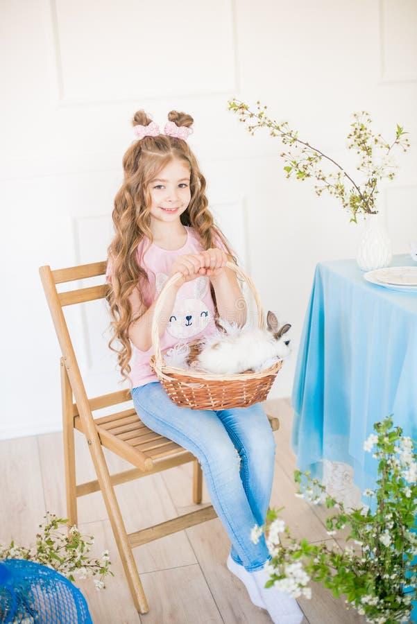 Liten gullig flicka med l?ngt lockigt h?r med sm? kaniner och p?skdekoren hemma p? tabellen arkivfoton