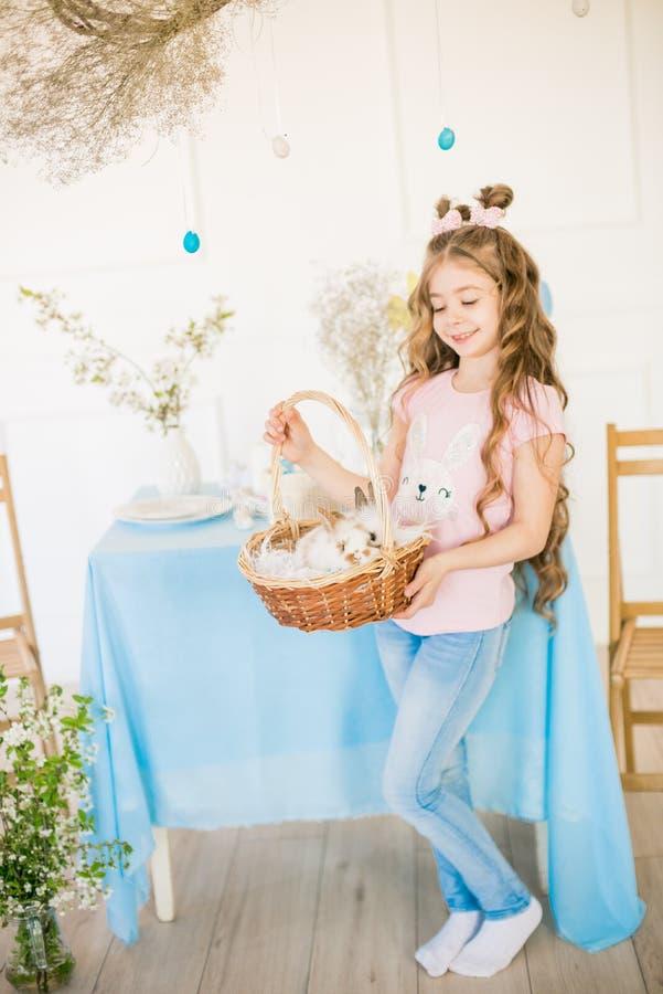 Liten gullig flicka med l?ngt lockigt h?r med sm? kaniner och p?skdekoren hemma p? tabellen royaltyfri bild