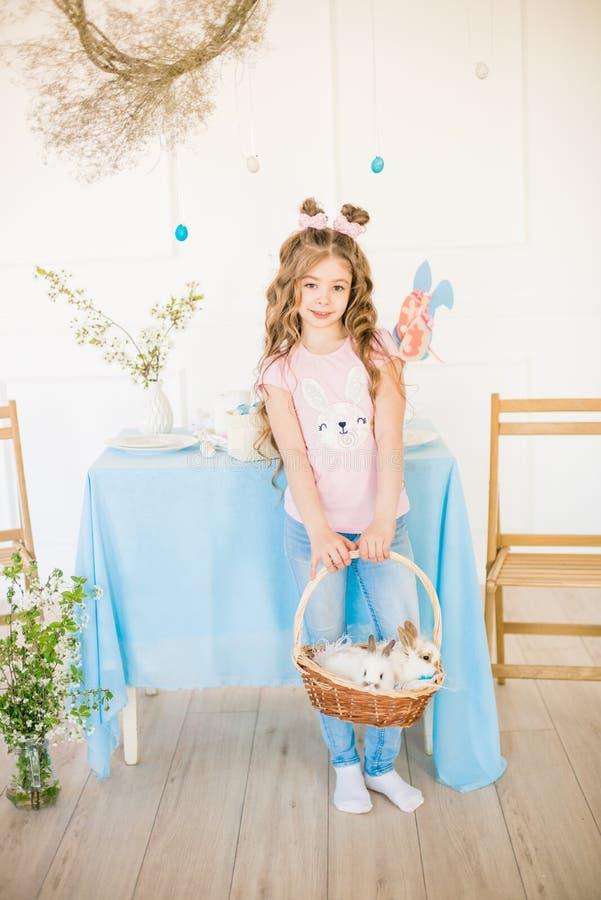 Liten gullig flicka med l?ngt lockigt h?r med sm? kaniner och p?skdekoren hemma p? tabellen royaltyfri foto