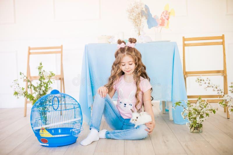 Liten gullig flicka med l?ngt lockigt h?r med sm? kaniner och p?skdekoren hemma p? tabellen royaltyfria bilder
