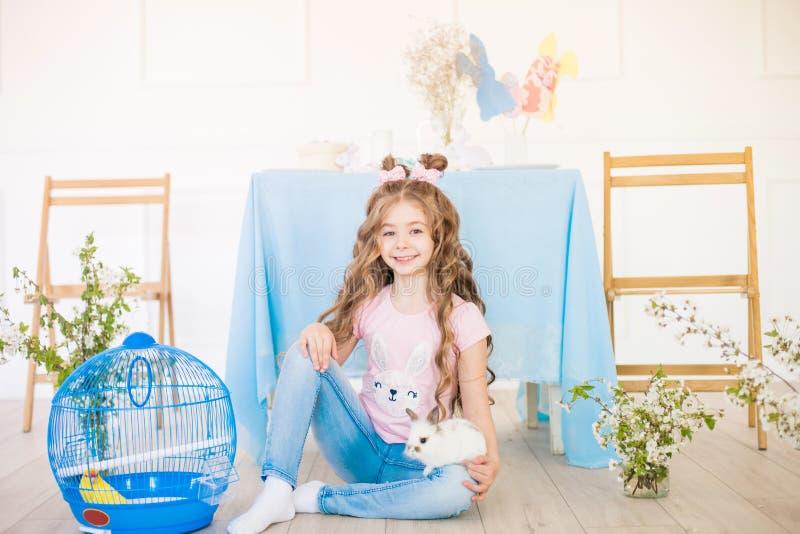 Liten gullig flicka med l?ngt lockigt h?r med sm? kaniner och p?skdekoren hemma p? tabellen royaltyfri fotografi