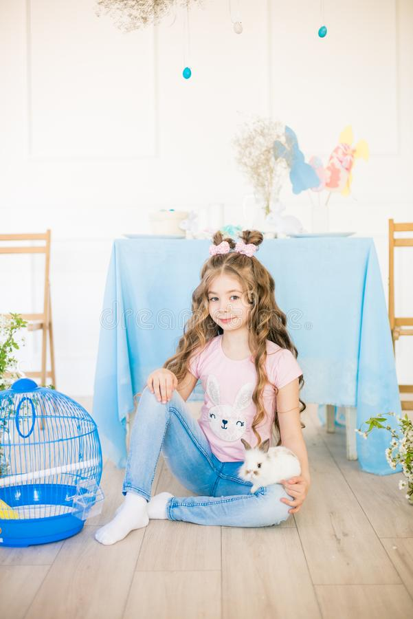 Liten gullig flicka med l?ngt lockigt h?r med sm? kaniner och p?skdekoren hemma p? tabellen royaltyfria foton